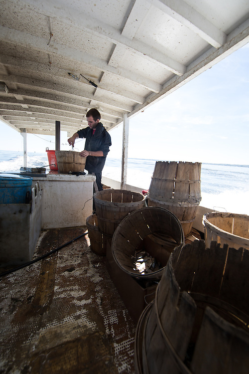 Chris Shipley sorts through the days catch and secures the tops on the baskets filled with crab as they head home. | October 11, 2015