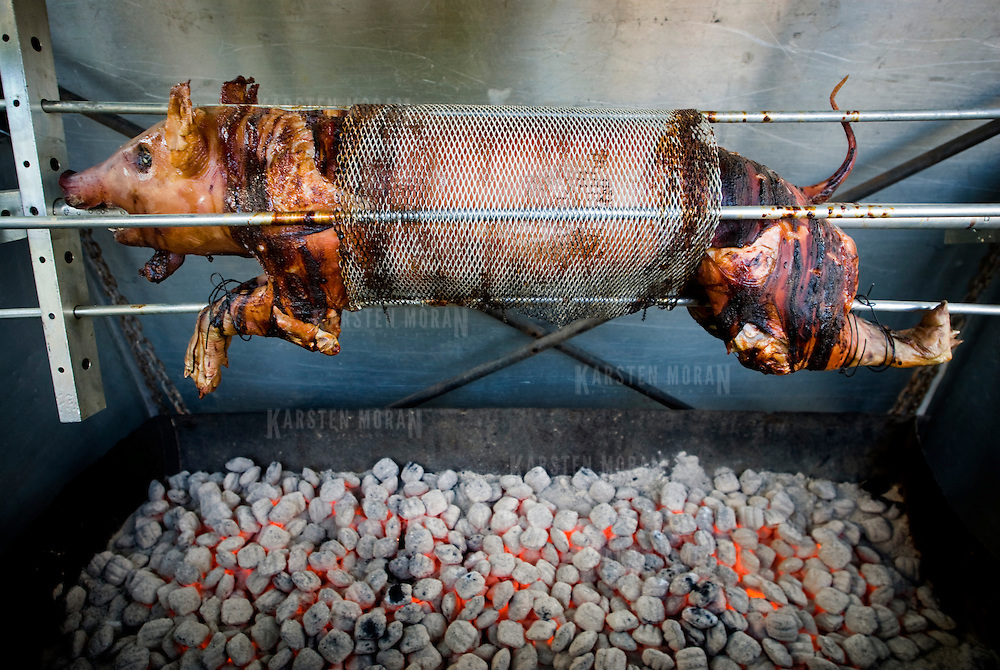 A pig, being roasted on a spit, at the 9th avenue New York City food festival.