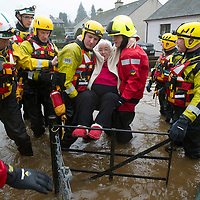 Flooding in the village of Comrie, Perthshire after heavy rain caused the River Ruchil to burst it's banks and flood the surrounding streets.....  Firefighter's rescue and elderly resident from her house on Glebe Road as the floodwater rises. <br />