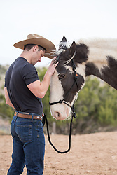 cowboy petting a painted horse