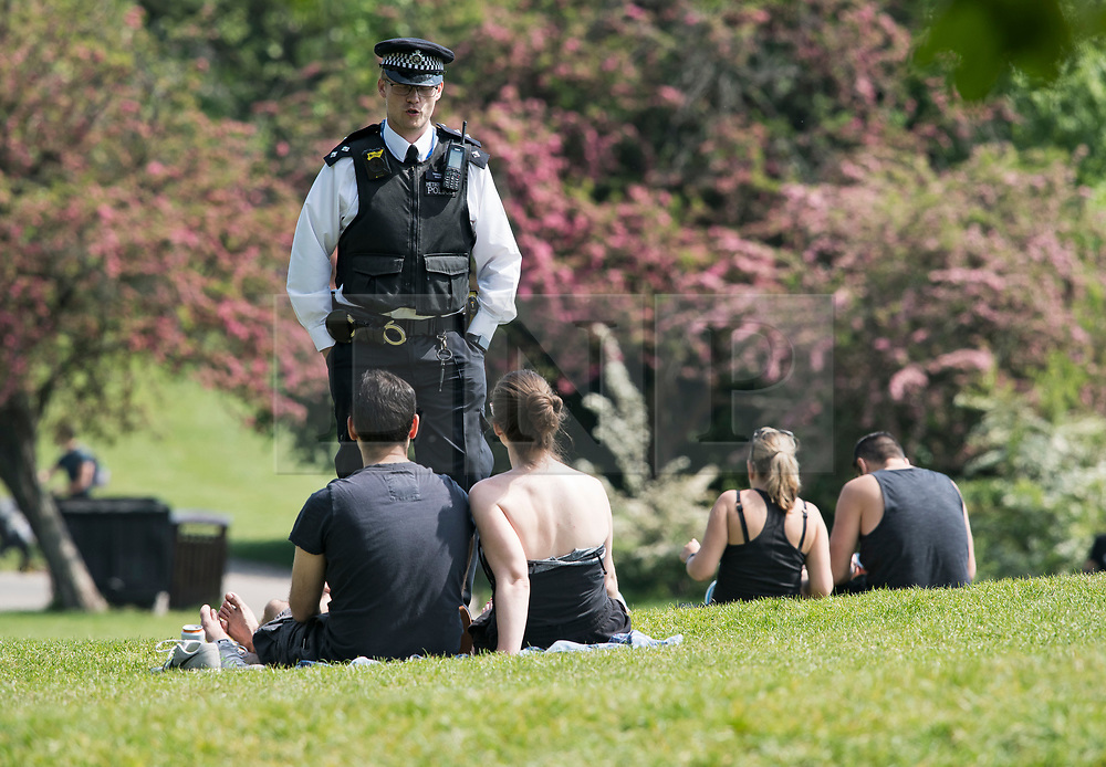 © Licensed to London News Pictures. 08/05/2020. London, UK. Police officers talk to members of the public lying down on Primrose Hill in North London, during lockdown. Government is set to announce measures to easy lockdown, which was introduced to fight the spread of the COVID-19 strain of coronavirus. . Photo credit: Ben Cawthra/LNP