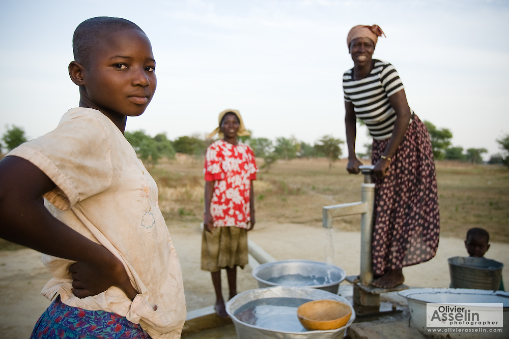 Women and children get water from a hand pump outside their village.