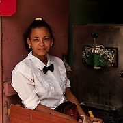Yumilla Cruz pauses for a portrait between serving customers ice cream at a small state-run sidewalk shop on the busy street Monte, in the innercity Havana neighborhood of Jesus Maria, where Cruz resides.  Small ice cream cones, made from milk powders due to lack of available dairy in the country, are sold to locals for several cents in Cuban Peso currency. The cones provide a small, cheap, treat and momentary break from the tropical heat. The heat can be particularly oppressive in inner-city Havana, where there is an excess of factory dust, diesel exhaust from busy roadways, a greater density of inhabitants, and little sea-breeze reaching the interior for relief.  Photo by Jen Klewitz