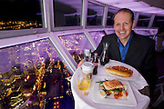 Neil Jones, the Director of Operations at the CN Tower in Toronto, Canada, with one day's worth of his typical food in the skypod of the tower. (From the book What I Eat: Around the World in 80 Diets.) The caloric value of his day's worth of food on a typical day in June was 2600 kcals. He is 44 years of age; 6 feet, 2 inches tall and 220 pounds.  The viewing platform is above the world's highest revolving restaurant, which revolves 360 degrees. The award-winning restaurant has awe-inspiring views and, for a tourist destination, surprisingly excellent food. The pricey entrance and elevator fee of about $25 per person is waived if you eat at the restaurant, making it cheaper to have lunch than to just see the sights. MODEL RELEASED.