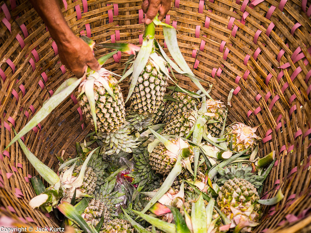 30 MAY 2013 - BANGKOK, THAILAND:  A basket of pineapple in a small fruit market near Bobae Market in Bangkok. Bobae Market is a 30 year old famous for fashion wholesale and is now very popular with exporters from around the world. Bobae Tower is next to the market and  advertises itself as having 1,300 stalls under one roof and claims to be the largest garment wholesale center in Thailand.   PHOTO BY JACK KURTZ