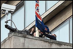 March 15, 2019 - London, England, United Kingdom: Shortly after New Zealand Terror Attack, New Zealand Embassy staff struggle to lower the New Zealand flag at half-mast due to high winds over the country's Embassy in London. Forty-nine people have been reported killed and 38 plus wounded in shootings at two mosques in Christchurch, New Zealand in a terror attack by far-right extremists. (Credit Image: © Pete Maclaine/i-Images via ZUMA Press)