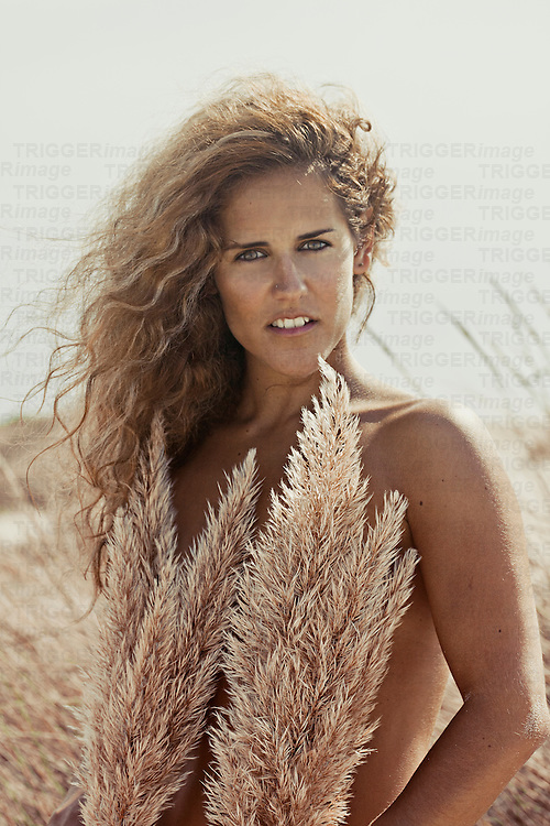 Portrait of a young woman with tanned skin and blonde curly hair holding summer plants in front of her chest and staring at the camera