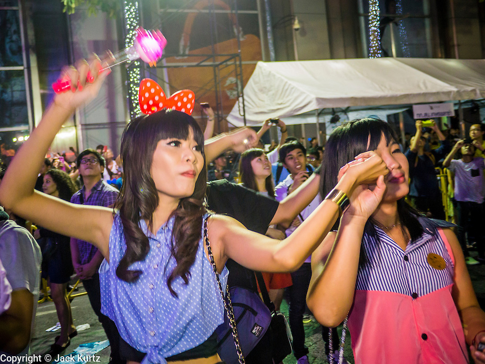 31 DECEMBER 2012 - BANGKOK, THAILAND: Thai women dance during the New Year's Eve party and countdown in Ratchaprasong Intersection in Bangkok. The traditional Thai New Year is based on the lunar calender and is celebrated in April, but the Gregorian New Year is celebrated throughout the Kingdom, especially in larger cities and tourist centers, like Bangkok, Chiang Mai and Phuket. The Bangkok Countdown 2013 event was called ?Happiness is all Around @ Ratchaprasong.? All of the streets leading to Ratchaprasong Intersection were closed and the malls in the area stayed open throughout the evening.    PHOTO BY JACK KURTZ