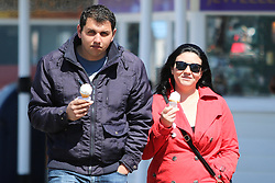 © Licensed to London News Pictures. 30/04/2015. Brighton, UK. A couple enjoys the warm weather on Brighton pier with an ice-cream, today Thursday April 30th 2015. Photo credit : Hugo Michiels/LNP