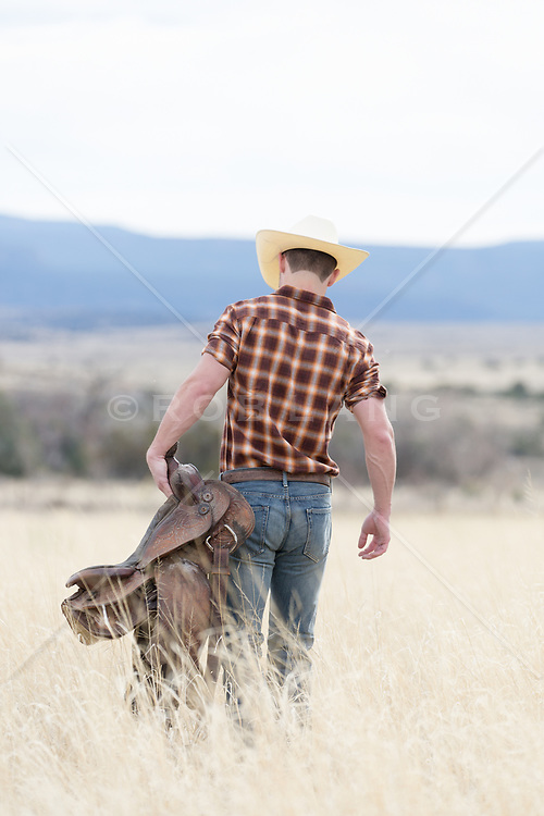 cowboy walking with a saddle through a field on a ranch
