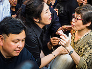 11 NOVEMBER 2016 - BANGKOK, THAILAND: YINGLUCK SHINAWATRA (center left) sells a sack of rice to a woman at a rice distribution sale in the Bangkok suburbs. Yingluck Shinawatra, the former Thai Prime Minister deposed in a coup in 2014, has started selling rice directly to Thai consumers. She buys the rice from farmers at market prices and then sells it to urban consumers at the price she paid. She said she's doing it to help out farmers, who are trying to deal with depressed prices. Yingluck is facing prosecution on corruption related charges going back to a rice price support scheme her government used to try to help farmers in 2011 and 2012. Even after the coup, she is still personally popular and hundreds of people showed up to see her at the rice distribution point at a mall in Samut Prakan province, in suburban Bangkok.   PHOTO BY JACK KURTZ