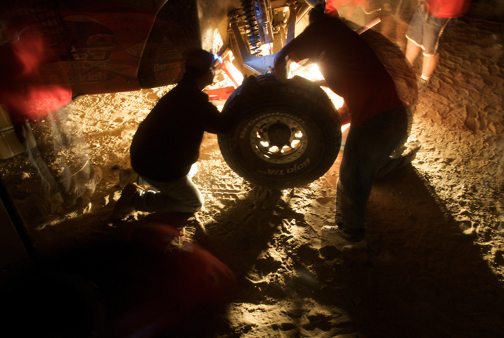Pits in the Baja 1000 often provide a spectacle as crews scramble to complete repairs in record time, by the light of headlamps and work lights while hoards of spectators watch from the shadows.