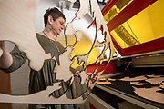 Kara Williams removes scrap wood from a lazer cutting machine at the Idea Lab in Zanesville. Photo by Ben Siegel
