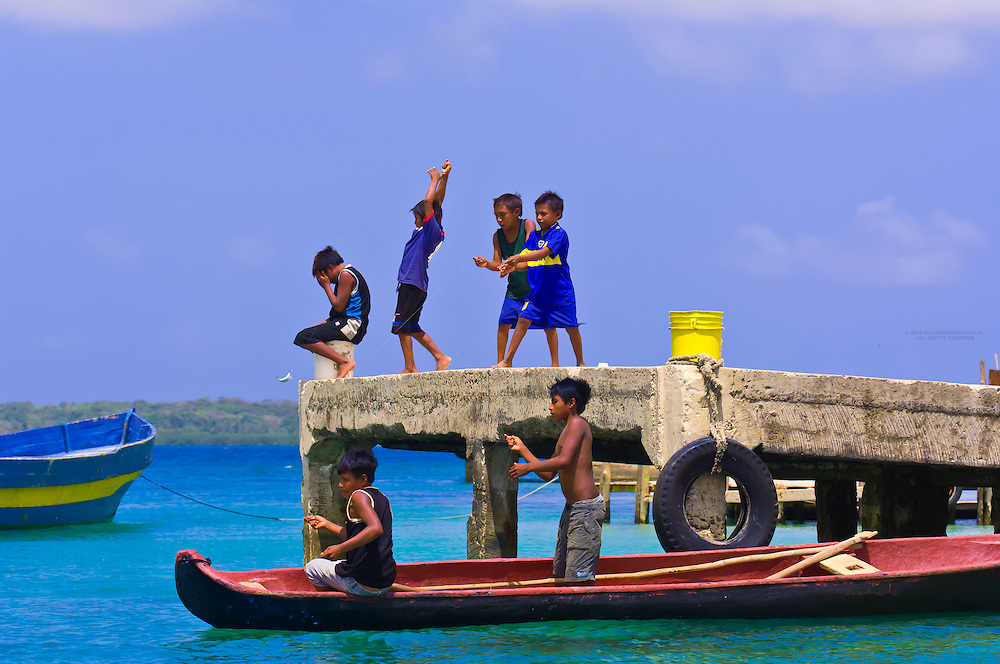 Kuna Indian boys fishing off a dock on Wichub Wala island, San Blas Islands (Kuna Yala), Caribbean Sea, Panama