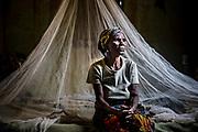 (Nombre señora) lleva toda su vida sufriendo la malaria. Es ciega y vive en Madzia, a 90 minutos del centro médico más cercano. Desde hace un año duerme bajo una mosquitera proporcionada por Cáritas. No ha vuelto a tener los síntomas. Madzia (Congo-Brazzaville) - Agosto 2015. Photo: Pablo Garrigos