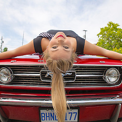 A beautiful young blonde, laying on a 1966 Ford Mustang convertible, with her hair flowing down over the center of the grille.