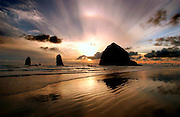 Haystack Rock is silhouetted by the setting sun off Cannon Beach in Oregon. The unique typography makes this one of the most scenic coastlines in the United States.