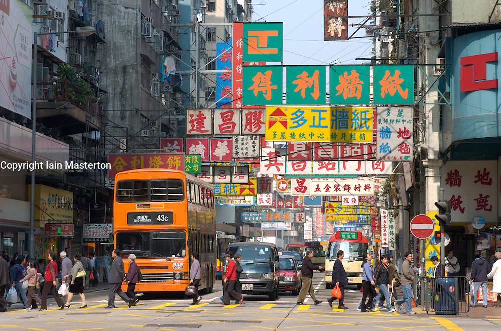 Busy street and many signs hanging above shops in Kowloon in Hong Kong