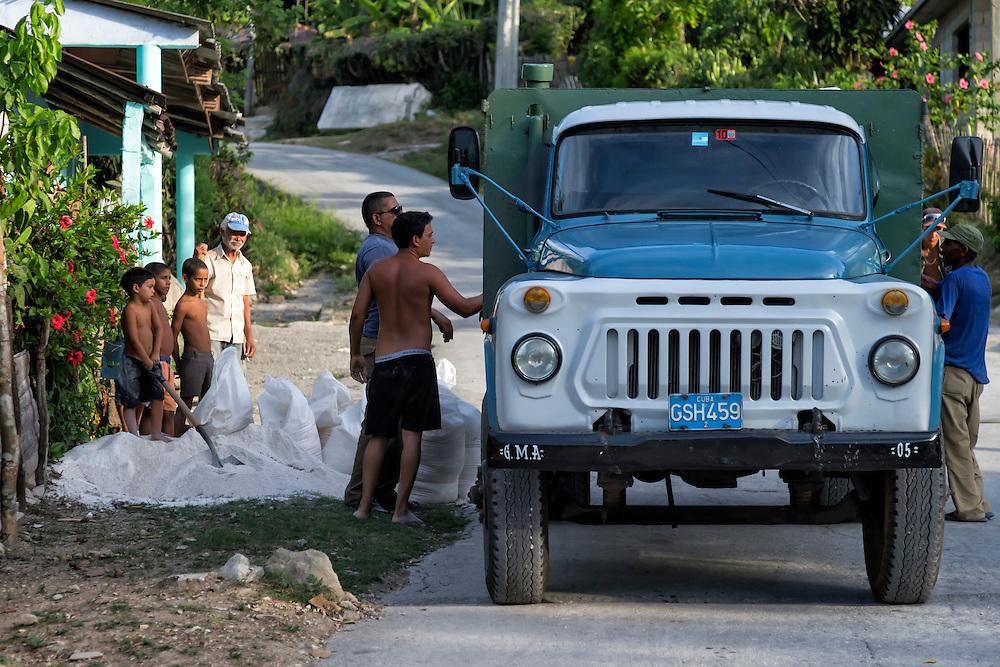 Bagging sand in Charco Redondo, Granma, Cuba.