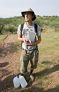 "Camp director Andrew ""Budge"" Burridge pauses for a brief rest on the morning patrol of the desert trails surrounding the No More Deaths camp in Southern Arizona. Each volunteer carries 2 4-litre jugs of water that is left along the trails for migrants passing through the area. The jugs are dated so the group has an idea of when people have travelled along a certain trail."