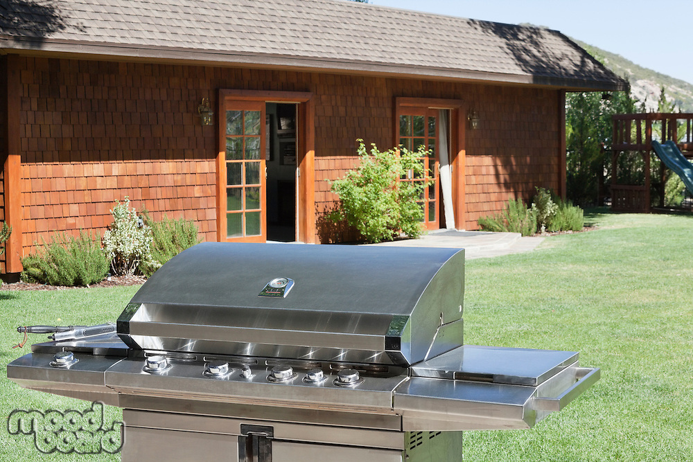 Stainless steel barbecue grill in front of house at lawn
