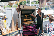 Cooking a cake on a spit over a wood fire, Sunday Market at Arreau, Hautes-Pyrénées, France.
