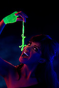 You woman opens her mouth to eat a glowing salamander dangling from her gloved hand.Black light
