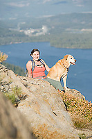 Young woman hiking with dog near Donner Pass, CA.