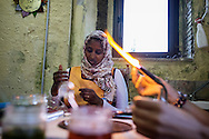 "A glass is blown over a flame while Darwa, 38 years old, Somali refugee works on a copper and glass sculpture. Rawda found employment with EU funds in the glassmaker workshop where the handmade souvenirs are sold to tourists. ""I don't feel like a foreigner or a stranger here in Riace, because these people are very kind and polite. I got a job here and my husband too, he got a UE project and now he is cleaning the streets of Riace, this is a new life for our family. My daughters couldn't go to school in Somalia, this is why 5 years ago I decided to escape with my husband and sons from our war torn home, now I have six children and I'm feeling really lucky.. I can give them a new future, they'll grow like world's citizens"".  RIACE (ITALY) 04/08/16"