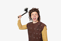 Portrait of angry young man in caveman costume holding axe against gray background