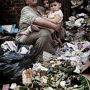 Una mujer frente a su casa abraza a sus nietos en un descanso durante el trabajo de separaci&oacute;n de los desechos org&aacute;nicos del resto de la basura recolectada. En medio del barrio de Manshiet Nasr a las afueras de El Cairo esta situado el asentamiento de Mokattam conocido como la &quot;Ciudad de la Basura&quot; , est&aacute; habitado por los Zabbaleen ,una comunidad de unos 45.000 cristianos coptos que viven desde hace varias d&eacute;cadas de reciclar los desperdicios que genera la capital egipcia: pl&aacute;stico, aluminio, papel y desechos &oacute;rganicos que transforman en compost . La mayor&iacute;a forman parte de la Asociaci&oacute;n para la Protecci&oacute;n del Ambiente (APE) una ONG que act&uacute;a en el &aacute;rea, cuyos objetivos son proteger el medio ambiente y aumentar el sustento de las recuperadores de basura de El Cairo. Seg&uacute;n la ONU, el trabajo que se realiza en Mokattam como uno de los diez mejores ejemplos del mundo en el mejoramiento medioambiental. El Cairo , Egipto, Junio 2011. ( Foto : Jordi Cam&iacute; )<br /> &laquo; less