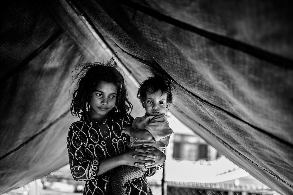A young girl of the Rajasthani nomadic tradation looks after her young charge in a camp in Manali, India. They travel north to the city every year in search of more lucrative work.