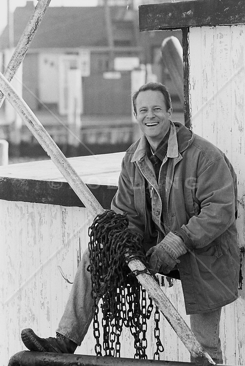 Man at a dock holding chains and smiling