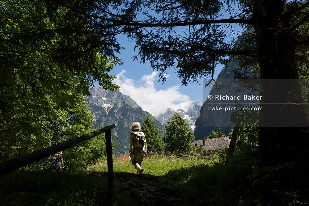 A walker emerges into sunlight in the Triglavski Narodni Park in the Slovenian Julian Alps, on 22nd June 2018, in Trenta, Triglav National Park, Slovenia. Nearby mountains are Kreiski 2050m, Pihavec 2419m, Dolina Zadnjica and Triglav 2864m.