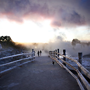 Visitors walk through the steam emitted from a spectacular geyser at sunset at Te Puia, Rotorua. Te Puia is the premier Maori cultural centre in New Zealand - a place of gushing waters, steaming vents, boiling mud pools and spectacular geysers. Te Puia also hosts National Carving and Weaving Schools and  daily maori culture performances including dancing and singing. Rotorua, 8th December 2010 New Zealand. Photo Tim Clayton.
