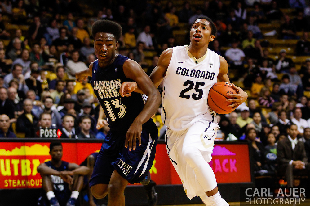 November 16th, 2013:  Colorado Buffaloes junior guard Spencer Dinwiddie (25) is fouled by Jackson State Tigers freshman guard Javeres Brent (13) on his way to the basket on a fast break in the second half of the NCAA Basketball game between the Jackson State Tigers and the University of Colorado Buffaloes at the Coors Events Center in Boulder, Colorado