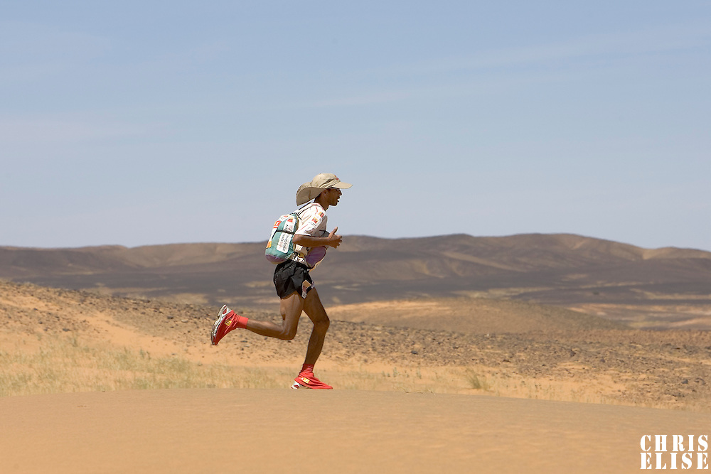 30 March 2007: Nine times winner of the men race #1 Lahcen Ahansal of Morocco runs across a dune in ergg Znaigui en route to check point 3 during fifth stage of the 22nd Marathon des Sables between west of Kfiroun and erg Chebbi (26.22 miles). The Marathon des Sables is a 6 days and 151 miles endurance race with food self sufficiency across the Sahara Desert in Morocco. Each participant must carry his, or her, own backpack containing food, sleeping gear and other material.