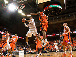 Virginia forward Mike Scott (32) skies for a layup past Clemson forward/center Trevor Booker (35).  The Virginia Cavaliers defeated the #12 ranked Clemson Tigers in overtime 85-81 at the John Paul Jones Arena on the Grounds of the University of Virginia in Charlottesville, VA on February 15, 2009.