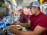 30 JULY 2019 - DES MOINES, IOWA:  ALDA, a Westmoreland Concessions worker, dips hotdogs into the corn dog batter in the Westmoreland corn dog stand on the Iowa State Fair fairgrounds. The Iowa State Fair Is one of the largest state fairs in the United States and runs for 10 days. In 2019, it runs from August 8 to 18. More than one million people attend the fair every year. Most of the food concessions at the fair don't open until August 3, when exhibitors arrive, but the Westmoreland Concessions corn dog stand opened on July 28. One of the stand's workers said a lot of people drive out to the fairgrounds the week before the fair to buy corn dogs because the fair is so crowded and concession lines are very long.   PHOTO BY JACK KURTZ