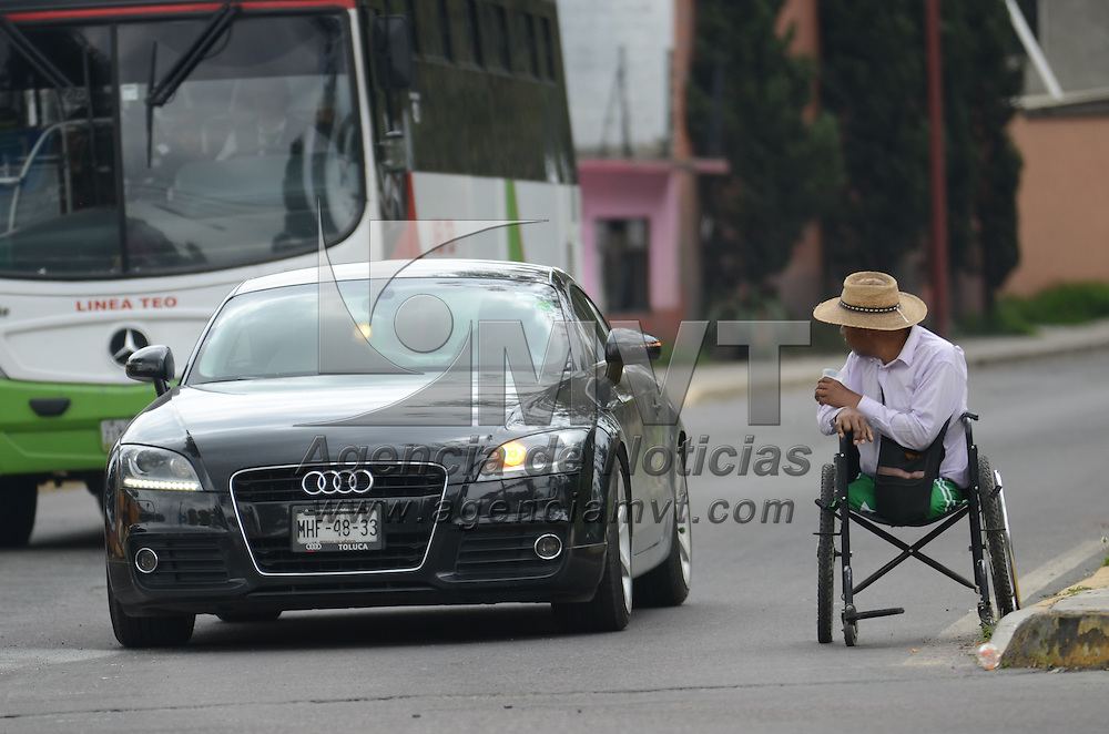 Metepec, México (Septiembre 1, 2016).- Un hombre en silla de ruedas se desplaza junto a los autos donde pide algunas monedas en el cruce de Av. Estado de México y Pino Suarez. Agencia MVT / Arturo Hernández.