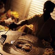 A man frying potato patties, Aloo Tikki, at night in Old delhi, India