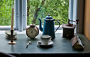 Old candle, clock, teakettle, cup, saucer, grinder, and book from generations long gone. The Hardanger Folk Museum was founded in 1911 in Utne, Norway.