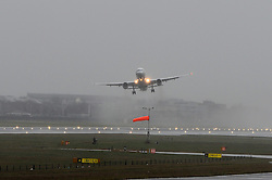 A plane looks uneven in the air as it takes over despite heavy rain and strong winds at Heathrow's Terminal 5.<br /> Christmas travellers leave for their festive holidays at Heathrow Airport. Monday, 23rd December 2013. Picture by Ben Stevens / i-Images
