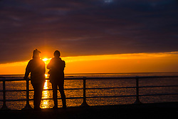 © Licensed to London News Pictures. 03/01/2018. Aberystwyth, UK. 03/01/2019. At the end of a grey dull and cold January day the sun makes a brief appearance as it sets over the Royal Pier  in Aberystwyth on the Cardigan Bay coast of west Wales.Photo credit: Keith Morris/LNP