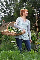 Woman holding vegetable basket in garden laughing