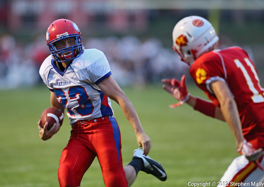 Decorah's Holt Johansen (23) tries to avoid Marion's Quinn Cannoy (11) on a run during the game between the Decorah Vikings and the Marion Indians at Thomas Park in Marion on Friday, August 31, 2012.
