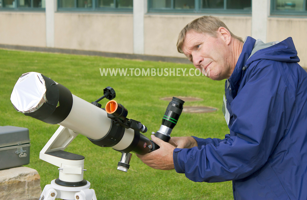 New Paltz, New York - A man sets up a refractor telescope with a solar filter on the State University of New Paltz campus to watch the Transit of Venus on June 5, 2012. Venus crossed in front of the sun and was visible as a small black disk. The next Venus transit will not occur until 2117.