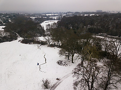 Hidden behind the fog and freezing rain is London's skyline while in the foreground a trail in the snow indicates a where a giant snowball was rolled as three inches of snow covers Hampstead Heath in North London. Hampstead, London, February 01 2019.