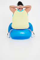 Overweight woman Exercising on exercise Ball back view