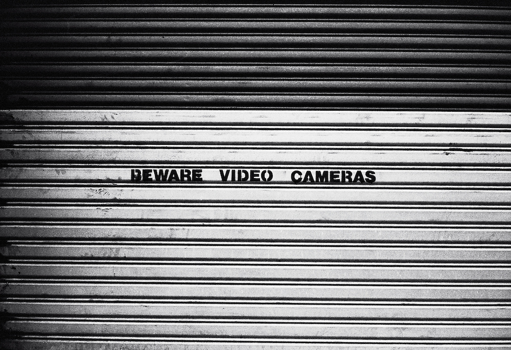 """Beware video cameras"" sign on security gate"